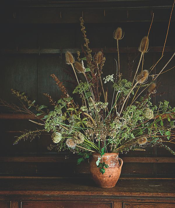 "Don't be defeated by the absence of flowers to bring in from the garden:  embrace dried seed heads and grasses instead.  Their delicate filigree of stems and leaf skeletons look great in a rustic  vase. Georgie Newbery ofCommon Farm Flowers used teasels*, dock,  loosestrife, mallow, hogweed, willow, yarrow, marjoram and wild carrot in  this airy arrangement, which will last all winter.  To keep it dust-free: ""Hoover from a distance to avoid obliterating the  arrangement itself.""  Tidy.   …"