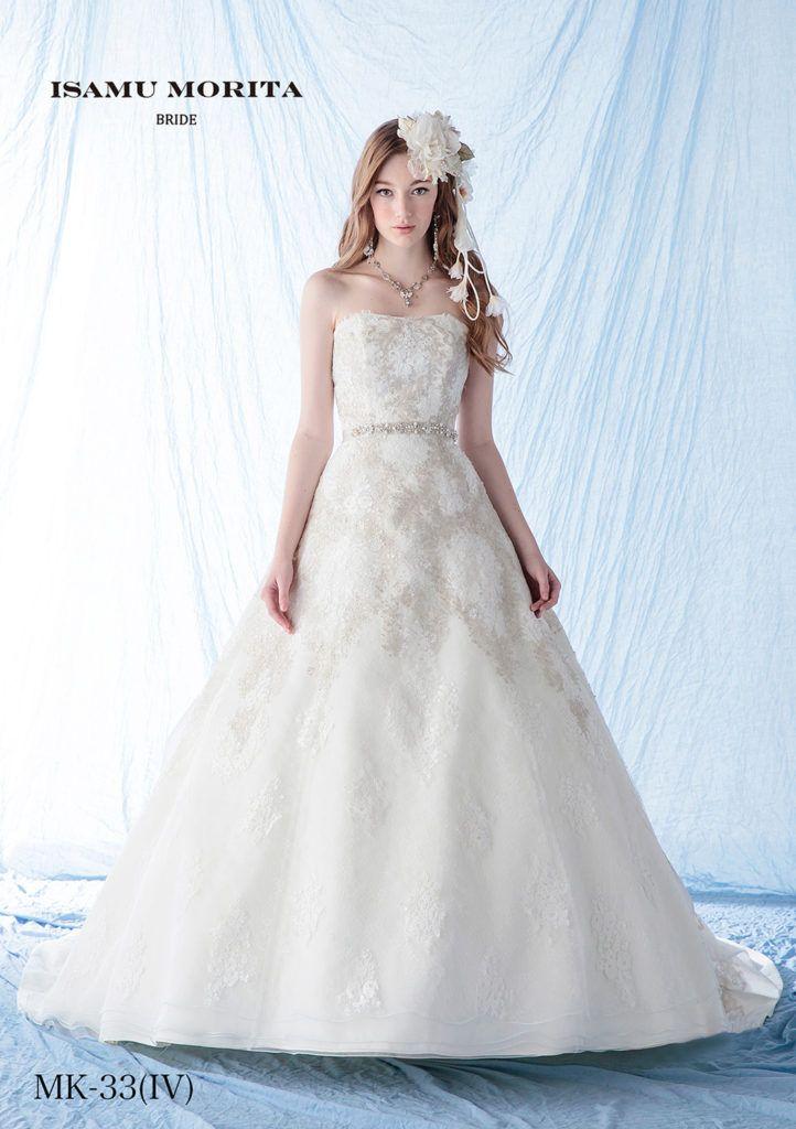 MK-33 - ISAMU MORITA ウエディングドレス - ビンテージライクな世界観を余すことなく表現したドレス。 シルバーのラメレースとオフホワイトのナチュラルレースを組み合わせ、ドレスの柄を細やかに構成し表現しています。 バックトレーンのクラシカルな世界観は圧巻の一言です。 アンティークレースにビジューベルトの組み合わせが人気のドレスです。動く度に揺れるフレアーな