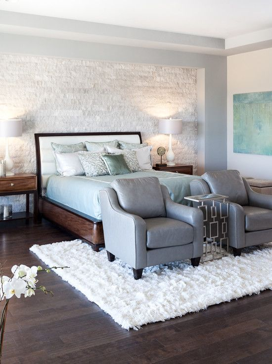 Master bedroom with dark wood floors, stone feature wall, white shag carpet and gray armchairs | Kat Alves Photography