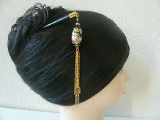 Hairstick with blue bead and three long gold chains modeled on a wig.