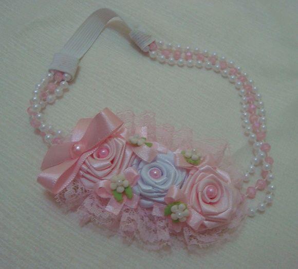 Faixa infantil em fios de pérolas rosa com branco e detalhes em rosas, laços e bicos. A circunferência total mede 45 cm. R$ 18,90