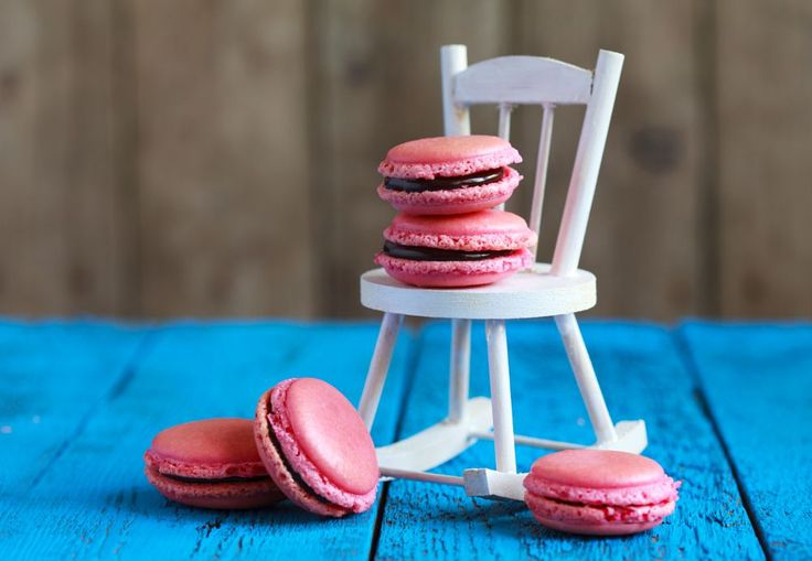 Homemade pink macaroons with chocolate filling and white decorative chair on a blue wooden table, se by OlgaPhoenix