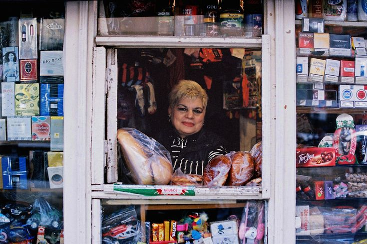 Kiosk - Tbilisi 2013 - Photography by Boogie: I was drawn to this image as a result of the way in which the subject is perfectly framed by the window of her stall. Despite the presence of the colourful items surrounding the subject, the viewer is still initially drawn the to face of the woman in the window. The blonde hair of the woman also strongly contrasts the dark, shadowed background behind her head.