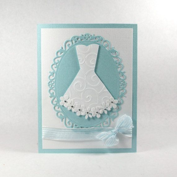 This bridal shower card is beautiful in blue and white. I designed this wedding shower card with bling paper, which has a shimmer to it. The gorgeous blue die cut is made of shimmer paper and has an intricate edge. The wedding dress embellishment is made of satin fabric, tiny pearls, tulle and flower appliqués. I adorned this card with blue sheer ribbon with ruffled edges. A bridal shower is the big day before the wedding day. The gifts, the family, the friends, the love and the anticipation…