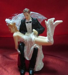 This could easily be a wedding cake topper of a tuxedoed guy and a stripper, not to be stereotypical. The bridal outfit could just be a costume.