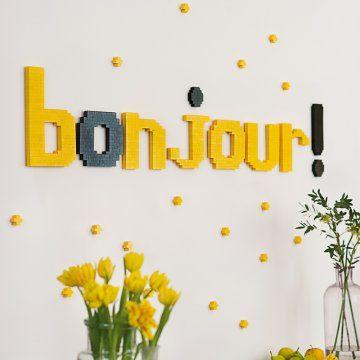 Mot bonjour avec lettres en lego en jaune et noir accrochées au mur
