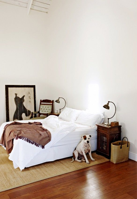 off white bedroom walls with white bed and leaning art on the floor - How To Clean Bedroom Walls