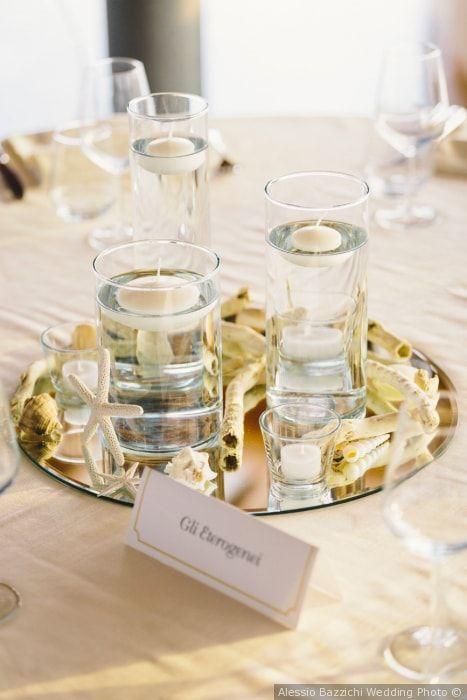 Centrotavola di nozze con candele e bicchieri e piatto d'argento. Per un matrimonio minimal chic.
