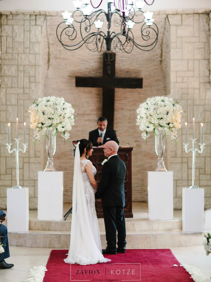 Classic wedding ceremony.Crisp white flowers,  and soft candle light. Huge flower arrangements with orchids and white roses. Luxe Wedding, Royal Wedding, Orchids, mass arrangements, large wedding flowers, luxury wedding.