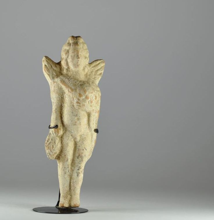 Greek Eros, hellenistic period, 2nd century B.C. Greek terracotta winged putto holding bunches of grapes, 16 cm high. Private collection