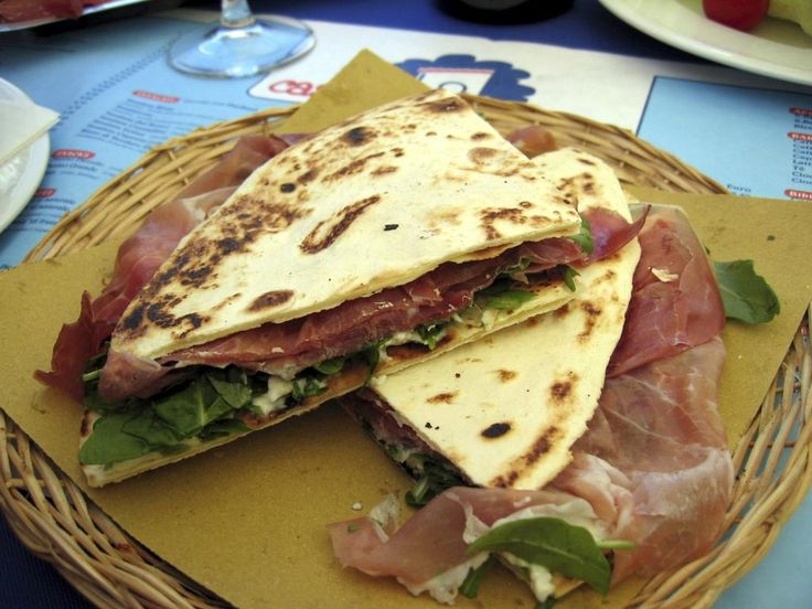 "Piadina (what I like to think of as the Italian quesadilla), a stuffed flatbread traditional to Emilia-Romagna makes PGI (Protected Geographical Indication) status- Ferrara is my pick for getting an optimal Piadina and visiting a cute Italian town. Look for shops/food stands written ""Piadineria"""