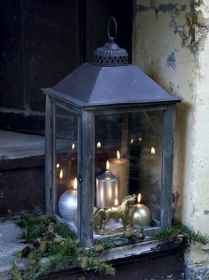 Candles of different shapes and sizes set in a big lantern. Silver and gold add a glamorous note to the rustic lantern.
