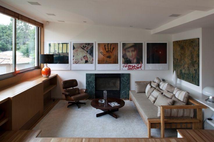O recanto de estar é muito acolhedor, dada a presença da lareira, instalada com a reforma assinada pelo arquiteto Arthur Casas. Obras de arte ocupam as paredes e podem ser admiradas da poltrona Charles Eames. O projeto original é do arquiteto Vilanova Artigas
