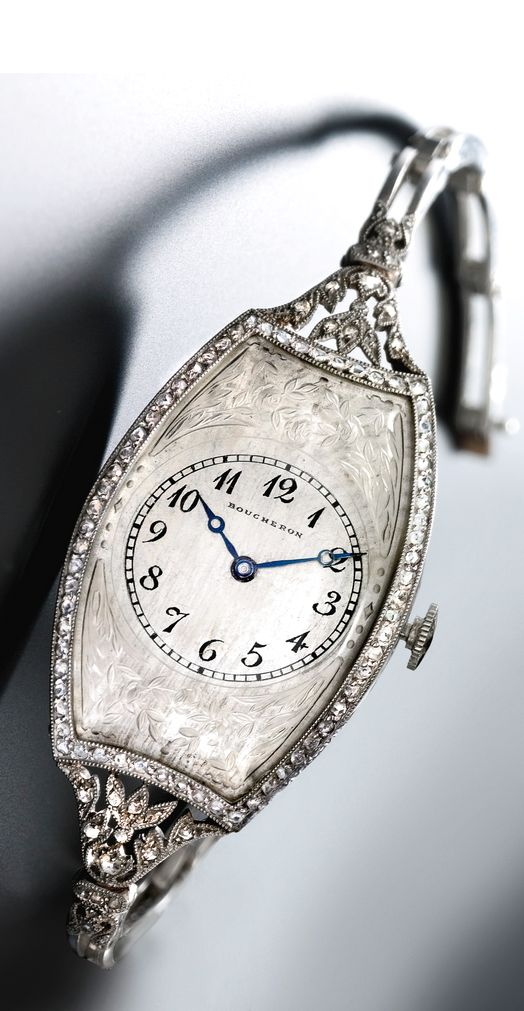 BOUCHERON A FINE AND RARE LADY'S PLATINUM, CARVED ROCK CRYSTAL AND DIAMOND-SET LARGE CURVED TONNEAU WRISTWATCH WITH BRACELET 1912 • circular manual-winding lever movement, 17 jewels • silvered dial, painted Breguet numerals, blued steel Breguet hands, finely engraved crystal with foliate motif • platinum tonneau-shaped case, rose-cut diamond-set bezel, pierced diamond-set lugs in floral motif, case back secured by five screws on the band • dial signed • with an associated platinum bracelet.