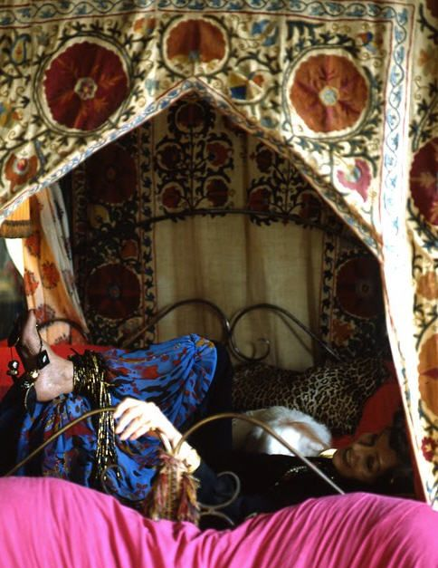 Maxime de la Falaise in her NYC loft bed - Embroidered and pieced Indian (?) hangings, leopardskin pillow, dog, funky harem pants, what appear to be bracelets or necklaces wrapped around her ankle. Hot pink pillow or sofa in front.  Layers and layers. (desire to inspire archives/2009/11/3)