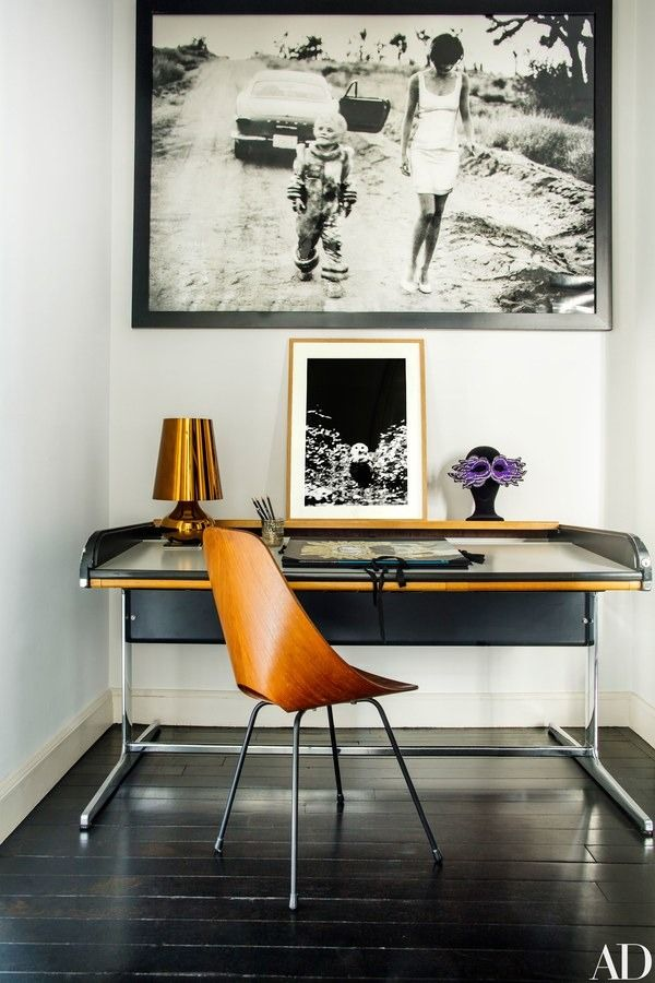 In the studio, a photo by Peter Lindbergh hangs over a Tambour rolltop desk by George Nelson for Herman Miller | archdigest.com