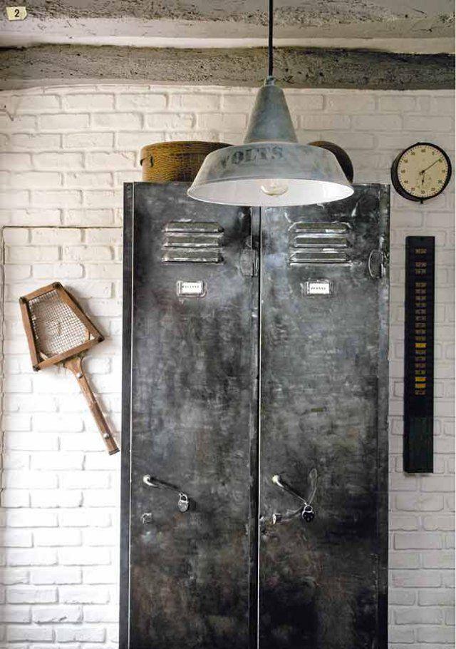 Devant un mur de pierre, un vestiaire d'usine patiné au graphite