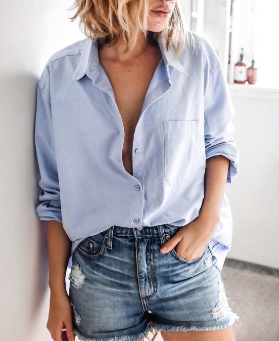 A light blue oxford shirt and blue denim shorts are a great outfit formula to have in your arsenal. Shop this look on Lookastic: https://lookastic.com/women/looks/light-blue-dress-shirt-blue-denim-shorts/17433 — Light Blue Dress Shirt — Blue Denim Shorts