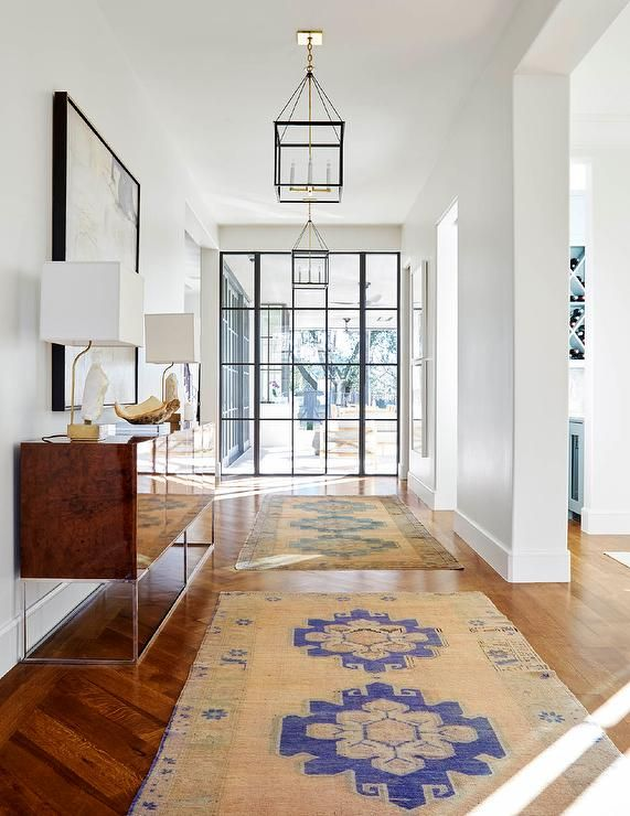 Beautiful foyer boasts a burl wood lacquered cabinet placed beneath a gold abstract art piece lit by natural light from a steel and glass front door and black and gold lanterns hung over blue and pink runners.