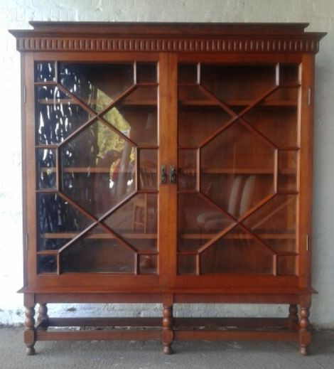 #NorthcliffAntiques Edwardian bookcase. Wood: Teak. Finish: Varnish. Bookcase details: moulded cornice and blind fretwork above two glass doors with original brass handles and astragal glazing bars enclosing four shelves on six bobbin turned legs joined by stretchers.  #Johannesburg #Bookcase #Teak #Library #Furniture #Wood #Antiques