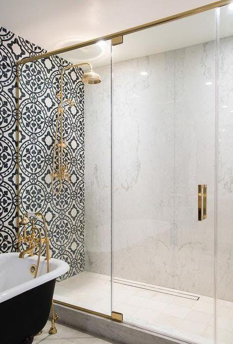 Marmeren inloopdouche met Marokkaanse tegelwand en gouden douchekop.