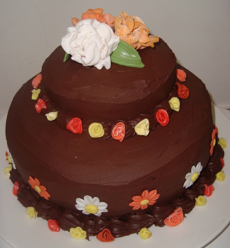 Torta al cioccolato farcita con mousse al cioccolato bianco e ricoperta con ganache al cioccolato fondente. fiori in pasta di zucchero
