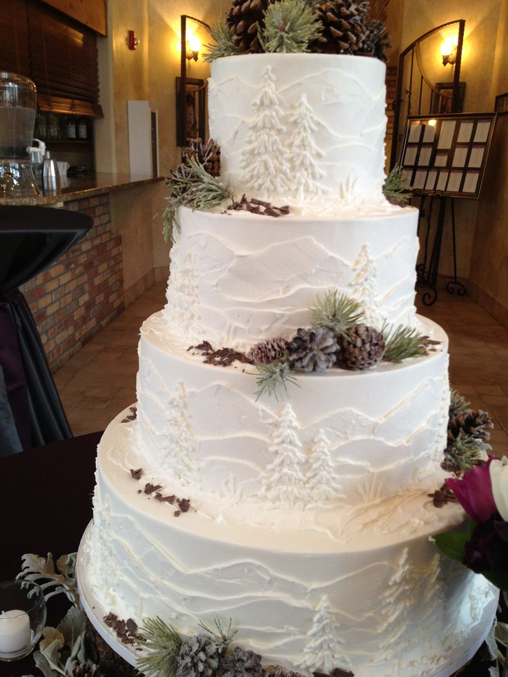 White frosted cake with mountains and pine trees, perfect for an outdoor colorado wedding!