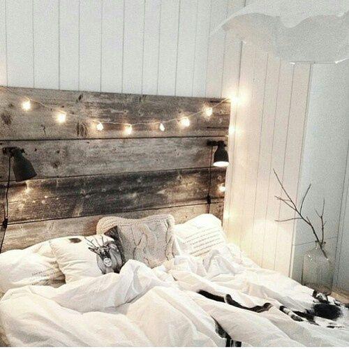 Ehebett. Großes Bett mit Lichterkette und Holzrückwand