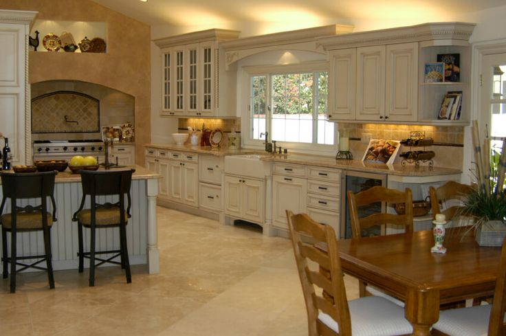 A very spacious contemporary country kitchen with an eat-in bar and a hardwood table. Subtle carved details above the windows and cabinets, along with the tile backsplash and floors mark this as French Country inspired, but the lighter, brighter white cabinets show the contemporary flair as well. A white farmhouse sink completes the look.