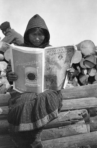 "Inuit woman reading ""Woman's Home Companion"""