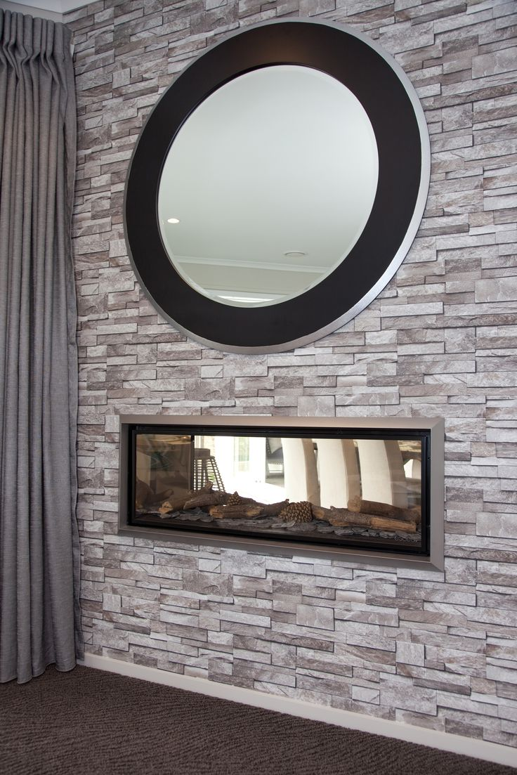 A double sided Escea vented fireplace is a feature of both the media room here, and dining area on the other side of the wall.