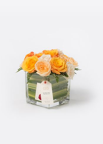 SAFI | Phormium yaprakları ile kaplanmış cam vazoda Creme de la Creme, Rosa Peach Avalanche ve Rose Confidential güller. | Bloom and Fresh