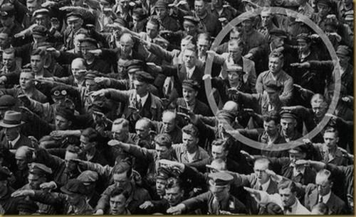 Ordinary people. The courage to say no.  The photo was taken in Hamburg in 1936, during the celebrations for the launch of a ship. In the crowd, one person refuses to raise his arm to give the Nazi salute. The man was August Landmesser. He had already been in trouble with the authorities, having been sentenced to two years hard labor for marrying a Jewish woman. We know little else about August Landmesser, except that he had two children. By pure chance, one of his children recognized her…