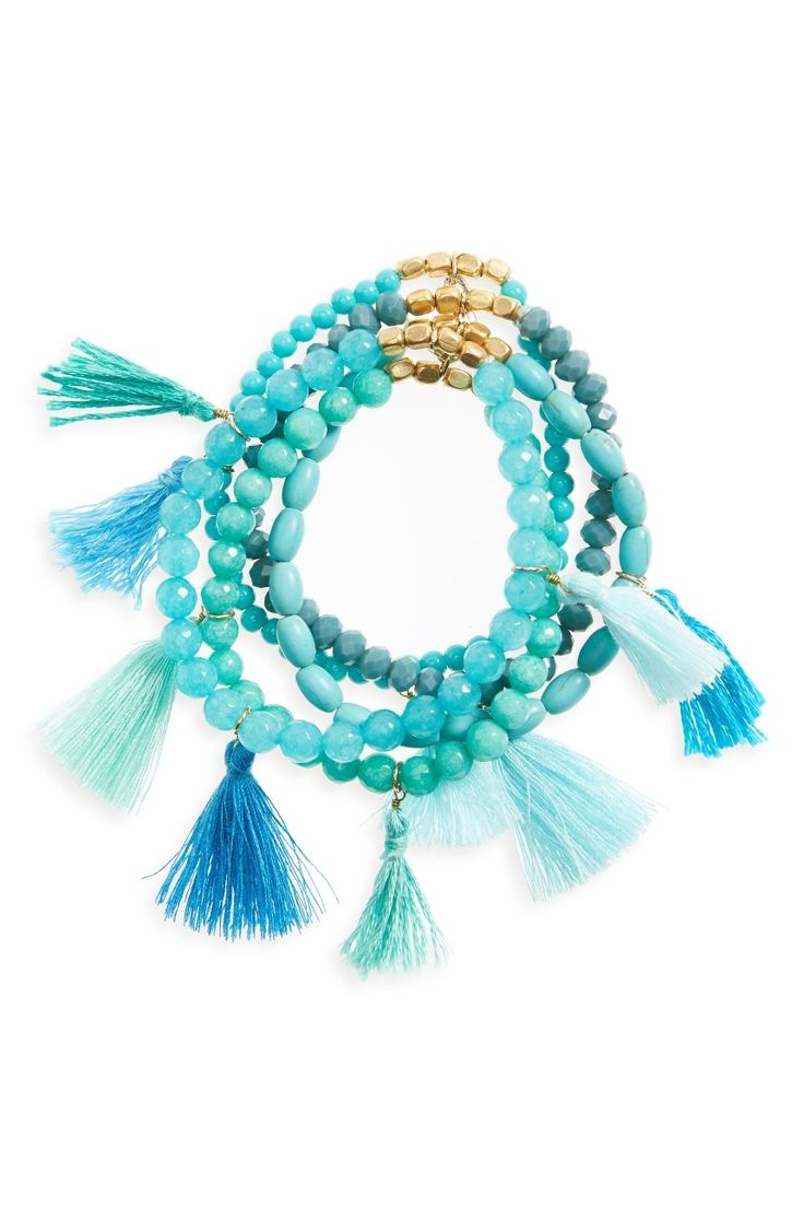 Various hues of aqua blue color the stones and tassels of a stretchy multistrand bracelet finished with golden beads.