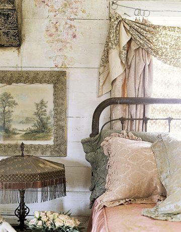 The guest bedroom is decorated with vintage sheets, curtains, and a lampshade with silk fringe.