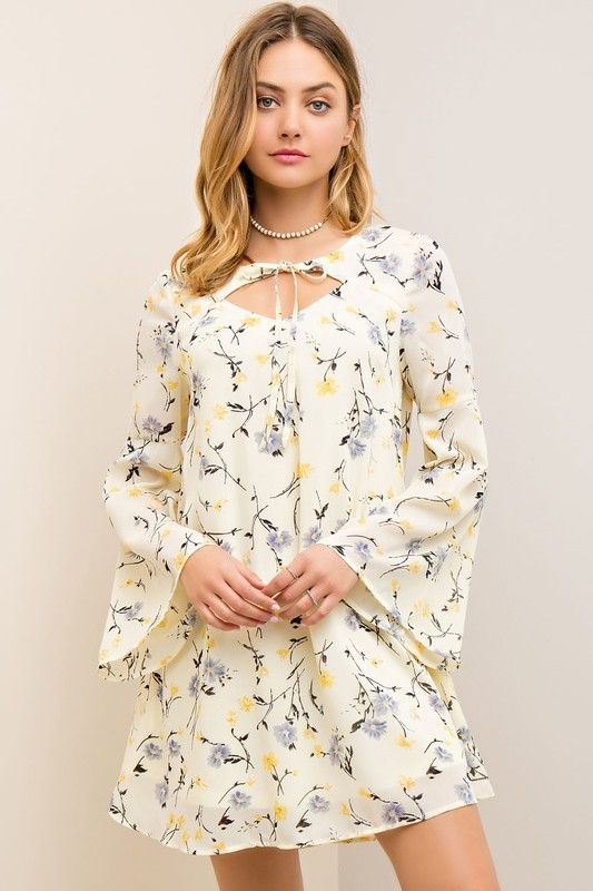 The Dainty Front Cut Out Dress just screams Easter! Pair this dainty long sleeve dress with some wedges for Easter with the family or pair with lace up flats for a cute work look!  Dainty Floral Front Cut Out Dress - Single Thread Boutique, $42.00 #dainty #floral #front #cut #out #dress #gorgeous #cream #blue #yellow #flowers #long #bell #sleeves #unique #womens #fashion #trendy #spring #singlethreadbtq #shopstb #boutique