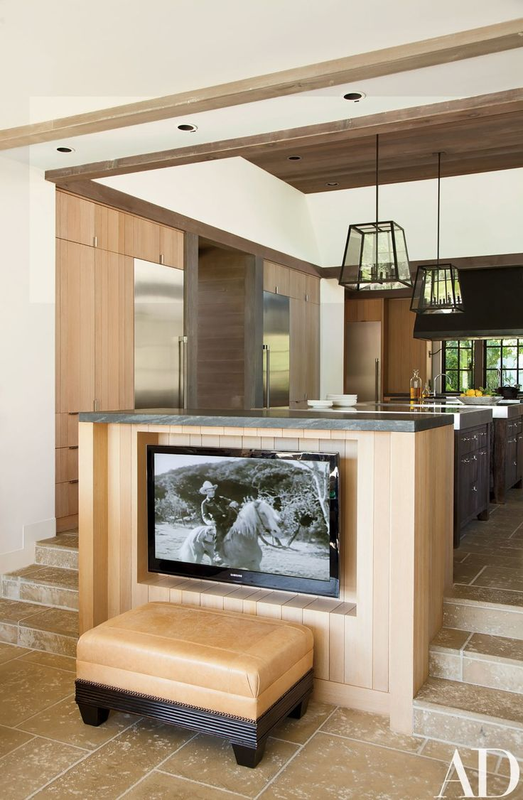 A Samsung television is tucked beneath the dining counter; the ottoman is by Summer Hill.