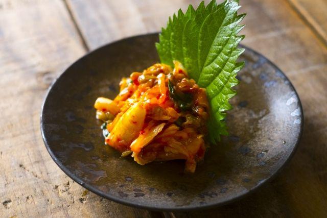 日本で一番売れている漬物、それは何だと思いますか? 日本には数多くの漬物が存在し、近年はその漬物離れが著しく、和食ブームとはいえ、漬物から日本人が遠ざかっています。 本来であれば、日本古来から保存食として親しまれてきた漬物。 保存食だけでなく、四季折々の野菜や食材を取り入れるために各地で発展してきた漬けものは、発酵食品の基本でもあり、近年は植物性乳酸菌が漬物には豊富ということが話題になってます。 ぬか漬け、しば漬け、白菜漬け・・・ そんな中、日本で最も親しまれている漬物は何かご存じですか? それはキムチ。 韓国の国民食ともいえる代表的な漬物であるキムチは、実は日本でもっとも消費されている漬物だったのです。 キムチといえば、白菜キムチが真っ先に思い浮かびますが、 ヤンニョム(ヤンニョン)というペースト状の「キムチのもと」を干して塩漬けにした白菜に漬け込んだもの、だけでなく、きゅうりや大根、かぶ、イカや魚介類にあえたものなど、実に様々な種類が存在します。…