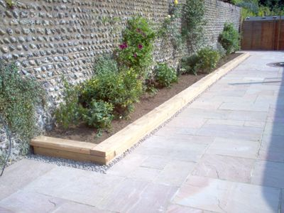 patio_rustington_indian_sandstone_flower_boarder_wooden_sleeper_surround_flint_wall.jpg (400×300)