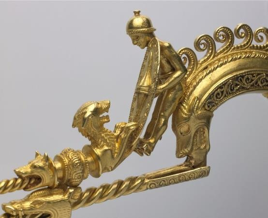 Celtic fibula from Northern Portugal, owned by the Brazanga family, circa 200-250 BC.   Another piece of ancient Celtic jewelry, a gold fibula, decorated with the figure of a naked warrior, wearing a Celtic helmet, with scabbard suspended from his waist and carrying a sword (scabbard and pommel are both of La Tene type).