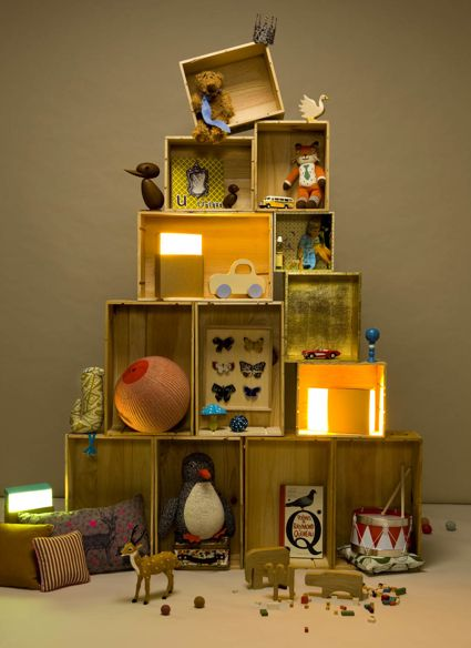 While this pyramid shape of goods and lighting might remind you of Christmas... it's an idea to tuck away for shop windows year 'round. (It's the top, askew box which makes the whole display SING!)