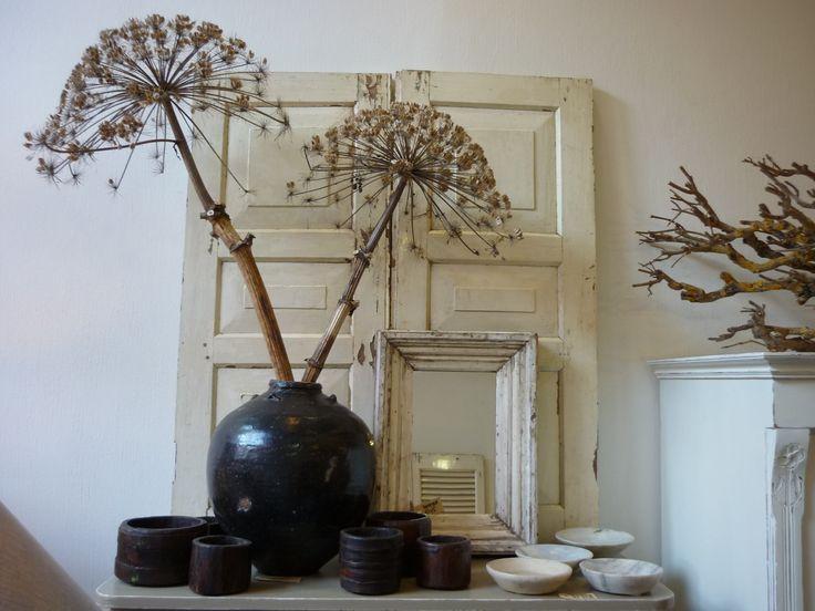 Interieur in creme en bruin; oude luiken, spiegel, pot en schaaltjes, takken bereklauw als decoratie