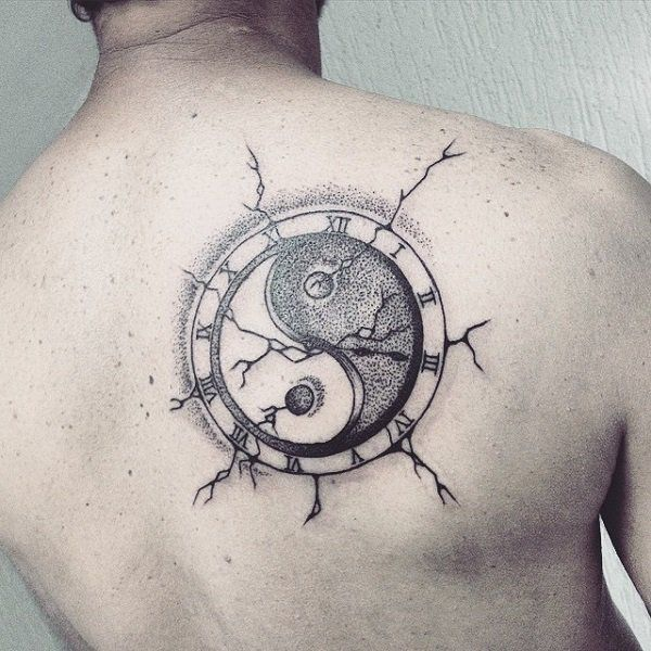 Black Yin Yang tattoo inked on the back, it depicts a Yin Yang symbol that apparently crashed on the person's skin with all the skin cracks inked around it.