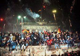 Jubelnde Menschen stehen auf der Mauer und feiern die deutsche Wiedervereinigung.