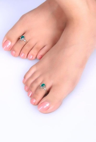 The unique drop shape design of these toe rings make these a worthy pick.Highlighted with an emerald stone this pair is made with sterling silver to adorn your delicate toe fingers.Comes with an adjustable wire enclosure with rounded & filed ends to ensure comfortable pinch free fit.  Dimension: Diameter Weight: 5.61 gm Color: Green & silver Closure: Adjustable Material: 92.5% sterling silver Finish: Hand crafted Inspiration: Banjara tribe, Rajasthan