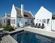 The Point Kommetjie The charm of this home is created with terracotta tiles and wooden furnishings coupled with a few modern touches. A large wood fireplace draws you into the living room and the inviting sitting room which is adjacent to the spacious indoor and outdoor dining area. Crisp, pure white linens pay homage to the sea-side town surrounds and large windows accentuate the natural beauty of Kommetjie- as well as letting in a lot of natural light. #locationshoot #photoshoot