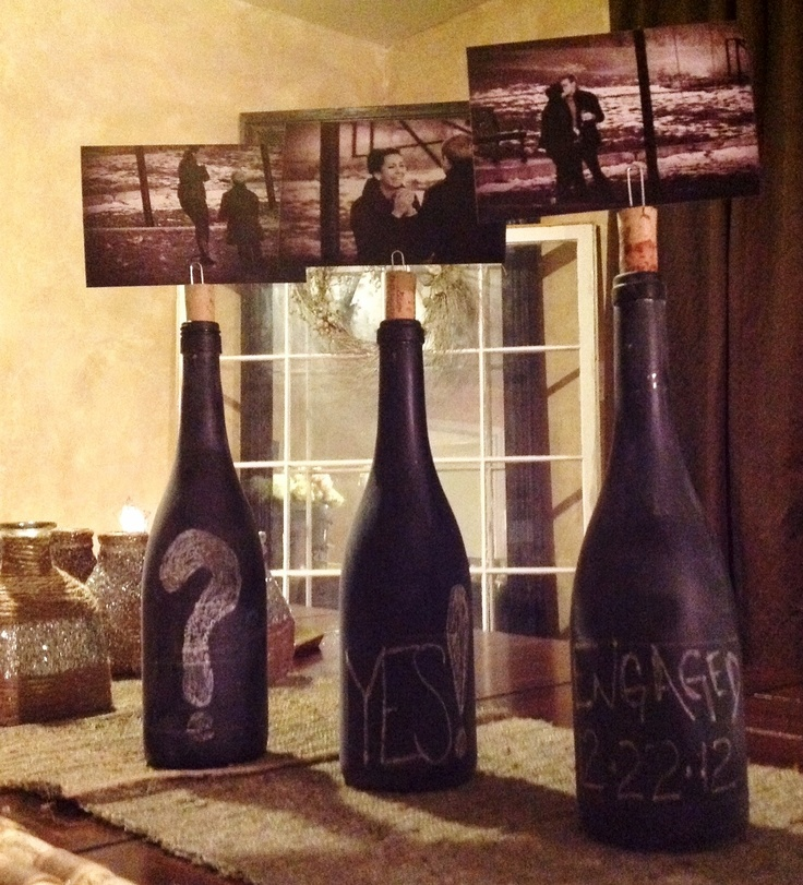 Cute idea for an engagement party Spray wine bottles with chalkboard paint, make a slit in the top of the cork for a paper clip & display engagement photos of the couple