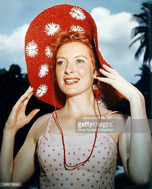 Scottish actress Deborah Kerr wearing a red sunhat with white flower motifs circa 1955