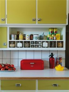 50's vintage kitchen. Cute lime (maybe?) cabinets against white tile with a super cute red bread box. I also love the built in open shelves!