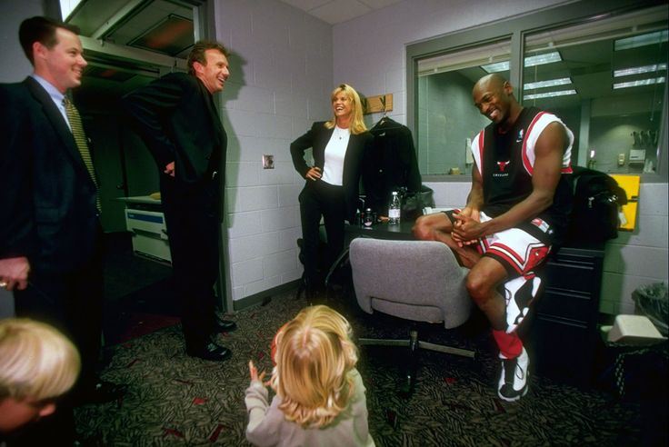 Joe Montana and his family share a laugh with Michael Jordan in his private room at the United Center in Chicago in April 1998. (Walter Iooss Jr.)